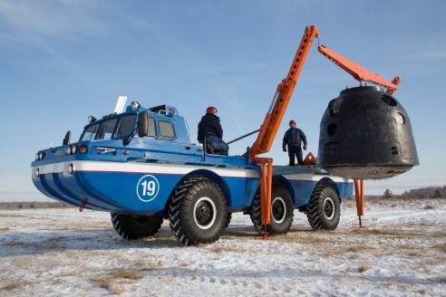 Погрузка  космической капсулы на поисково‑эвакуационную машину