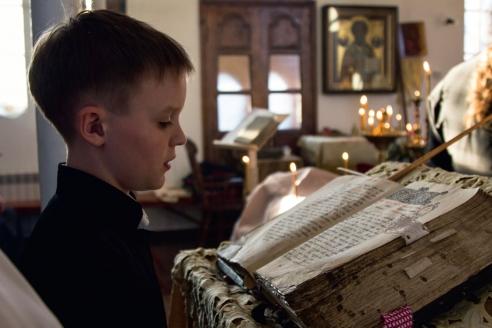 Юный пономарь читает службу Первого часа по старинной богослужебной книге