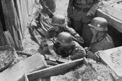 Расчёт немецкого пулемёта MG-34 ведёт наблюдение на позиции в польском селе. 1939 г.