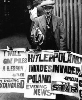 Британский продавец газет стоит около плакатов с заголовками газет: «Я преподам полякам урок — Гитлер», «Гитлер вторгается в Польшу», «Вторжение в Польшу».